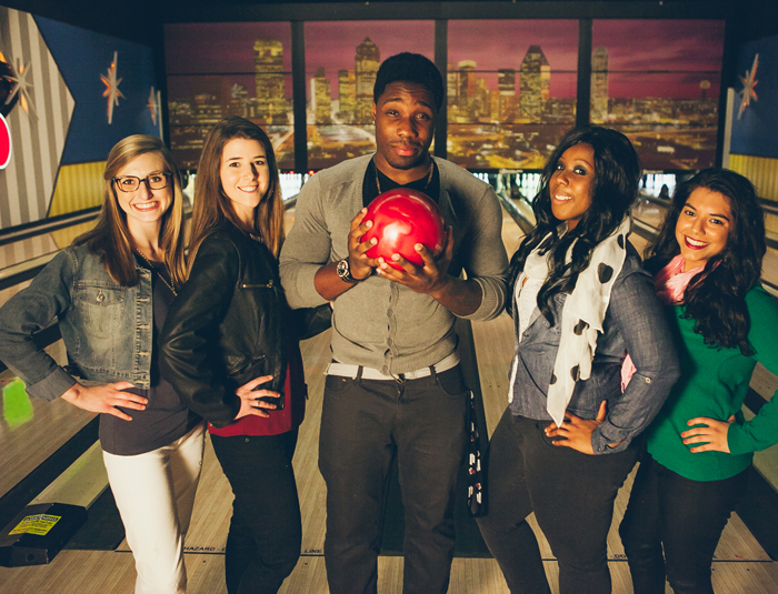 A group of people holding a bowling ball